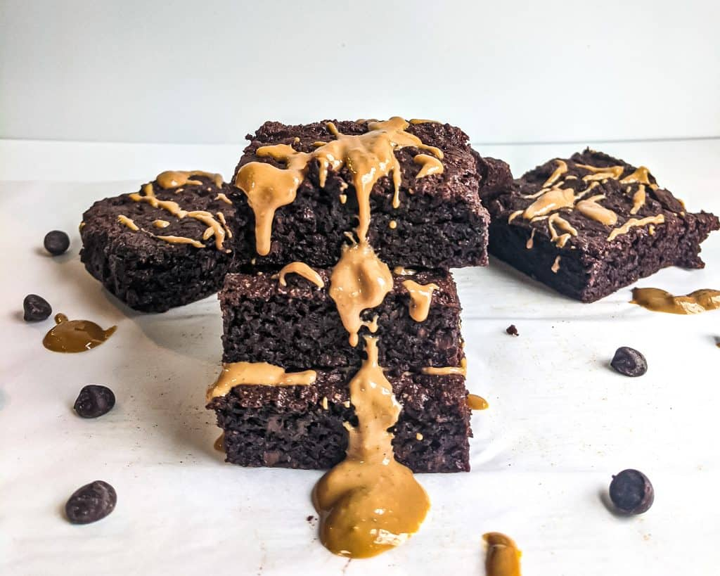 Tower of three flourless cashew butter brownies with additional brownies in background