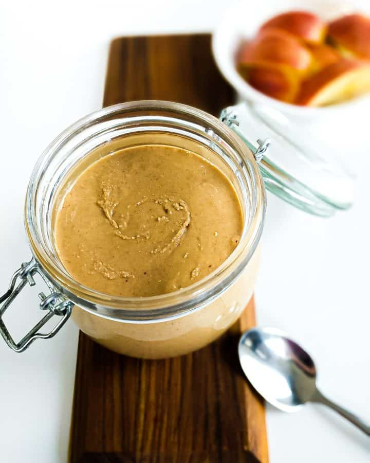 Cashew butter with apples in the background