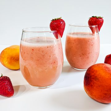 Two strawberry peach smoothies in glasses with peaches and strawberries surrounding. A strawberry hanging off of each glass.