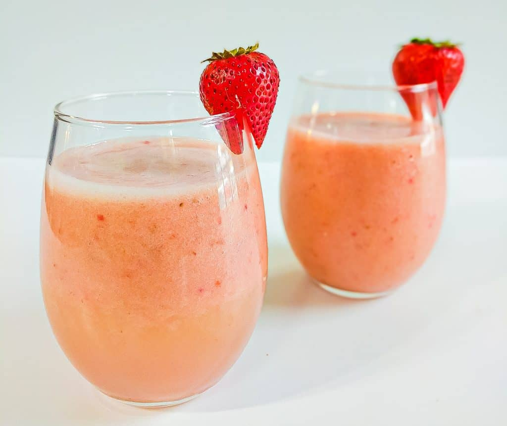 Two strawberry peach smoothies with an individual strawberry attached to each glass.