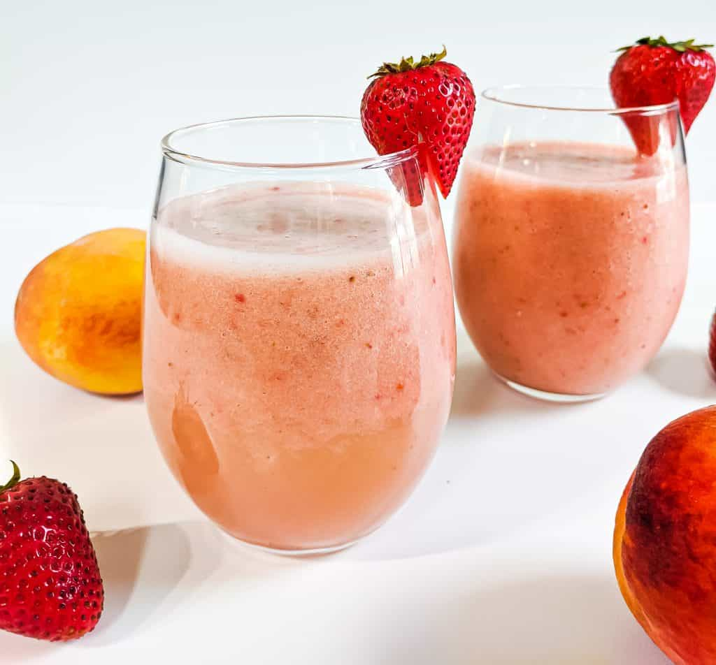 Two strawberry peach smoothies in glasses with an individual strawberry on rim of glass cup surrounded by strawberries and peaches.