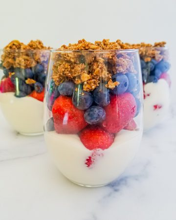 3 mixed berry parfaits with one in focus. Glass cup with yogurt on bottom then layered strawberries, blueberries and topped with granola
