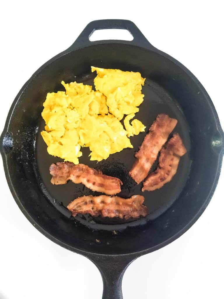 Skillet pan with cooked bacon and scrambled eggs