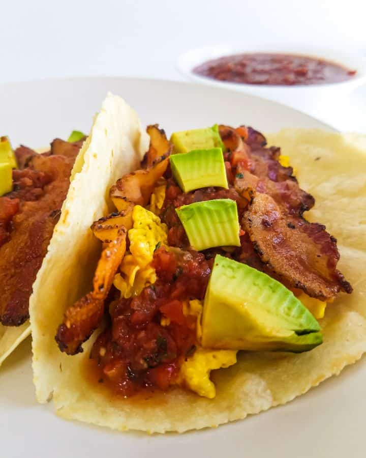 Breakfast taco on plate in tortilla shell with bacon, eggs, avocado and salsa. A cup of salsa in background.