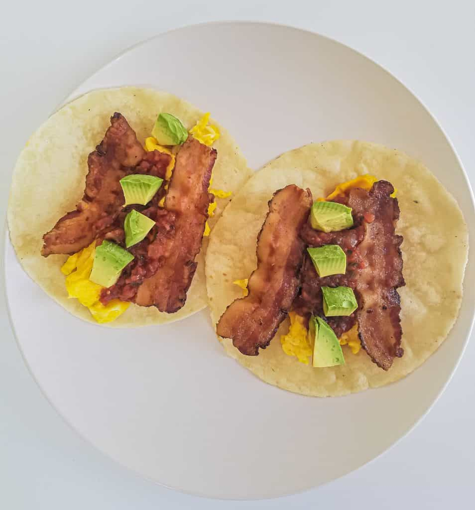 Two breakfast tacos laying open on plate