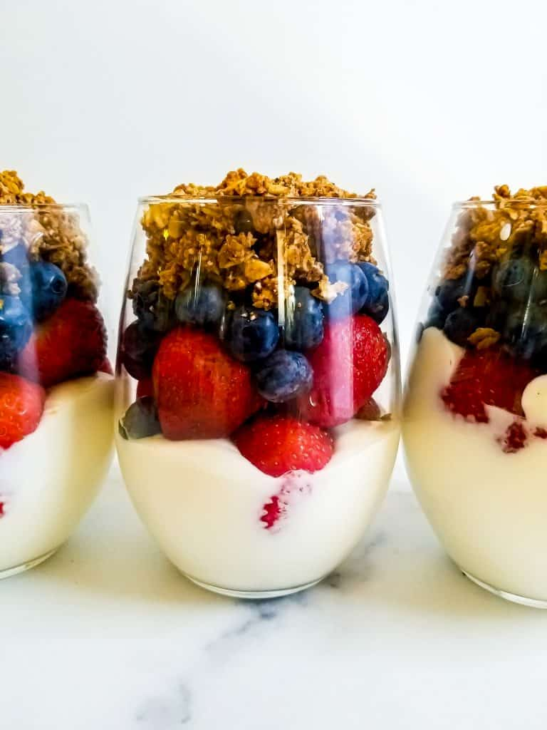 Three mixed berry parfaits with center in focus. Only can half of the ones on the end are visible.