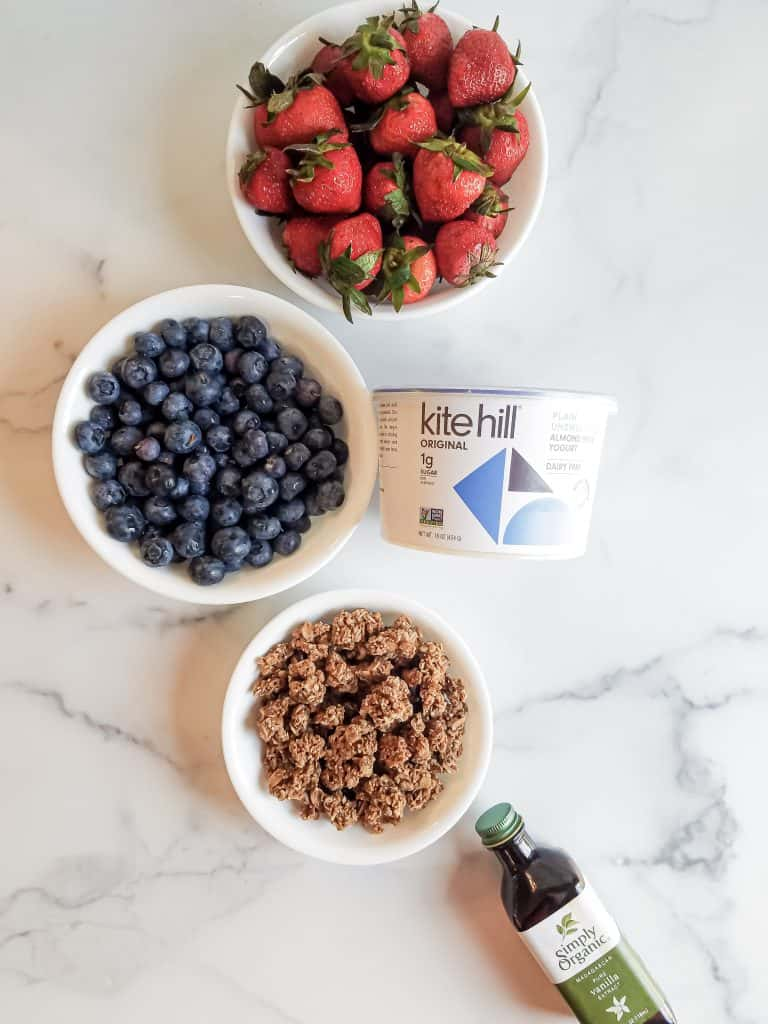 Ingredients for mixed berry parfaits- vanilla extract, granola, blueberries, strawberries and yogurt layed out