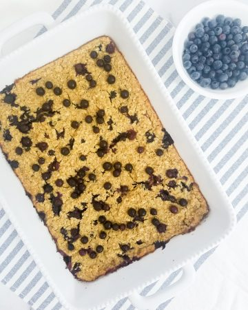 Pan with blueberry oatmeal bake on top of a blue and white stripe towel with a cup of blueberries next to it