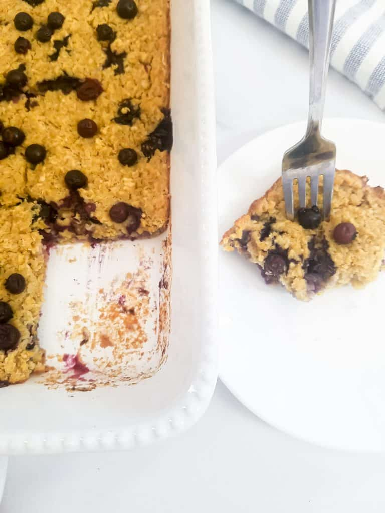Pan with piece of blueberry oatmeal bake missing. Piece is on plate next to pan with fork sticking in it