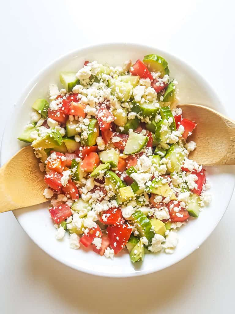 Bowl with tomatoes, cucumber, avocado, feta cheese and balsamic dressing with two wooden spoons on opposite sides of bowl to scoop salad