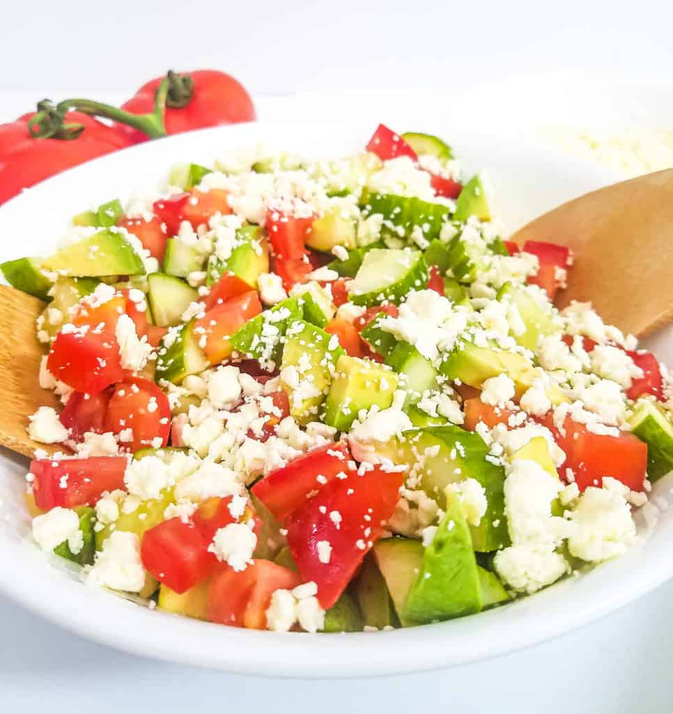 A bowl of tomato, cucumber, avocado salad with feta cheese with a wooden spoon in the bowl and 2 tomatoes in the background