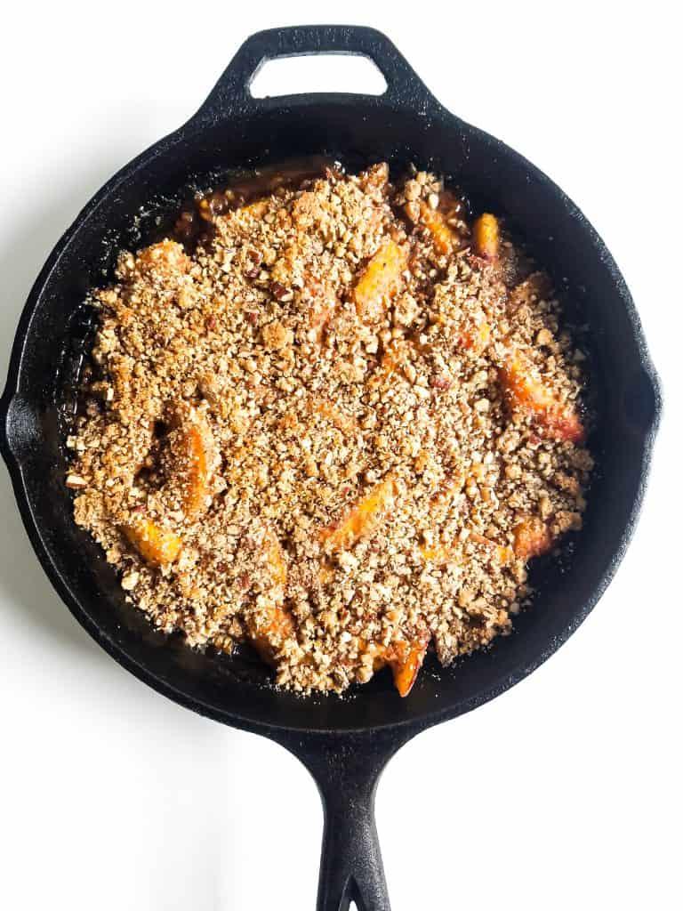 Baked peach crisp in black cast iron skillet