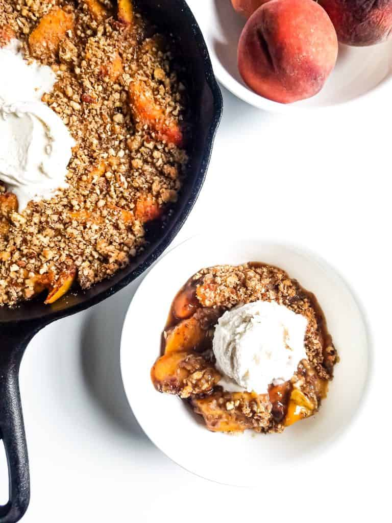 Bowl of peach crisp with ice cream on top next too skillet with crisp and ice cream. Bowl of peaches in right hand corner of photo.