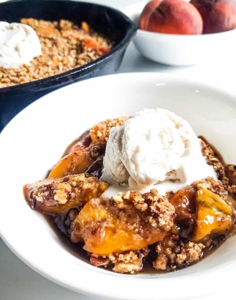 Close up of bowl with peach crisp topped with ice cream. Skillet with peach crisp and ice cream and bowl of peaches in the background